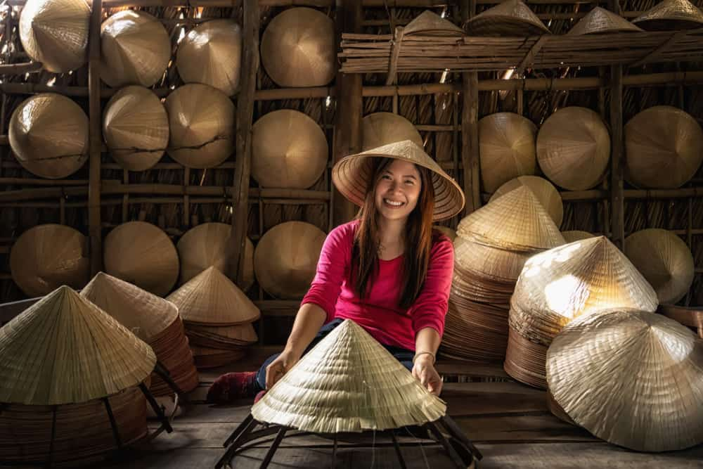 This is a woman inside a straw conical hat making shop with displays for sale.