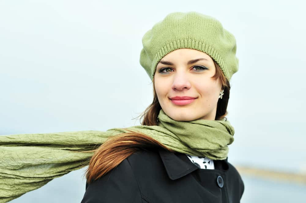A woman wearing a green knit tam cap with matching green scarf.
