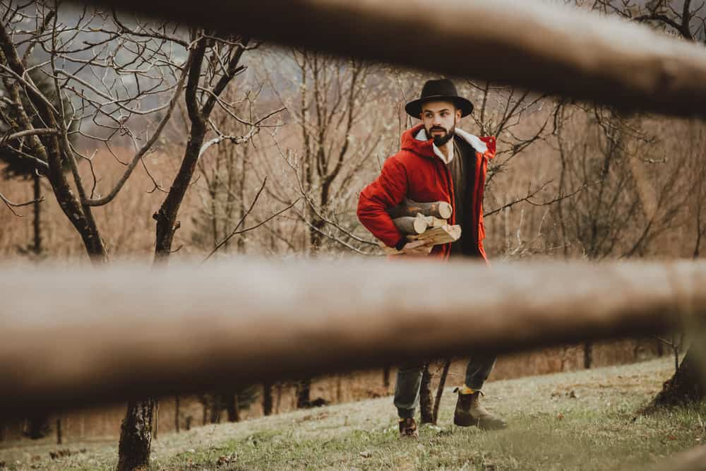 This is a bearded man in a ranch wearing a red jacket and a hat while collecting firewood.