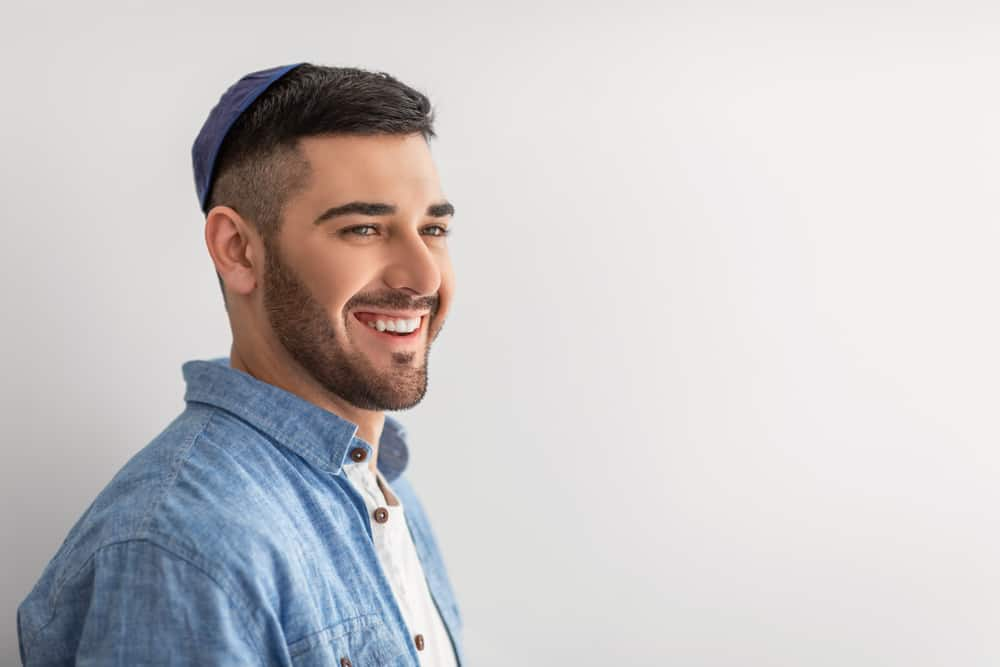 This is a close look at a man wearing a blue button shirt with a matching blue yarmulke.