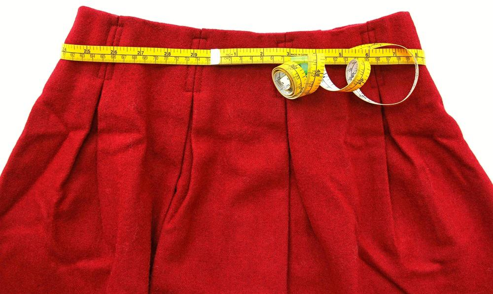 This is a red skirt with the waist section being measured using a measuring tape.