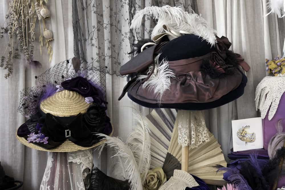 This is the window shop display of a Victorian shop featuring bonnets.