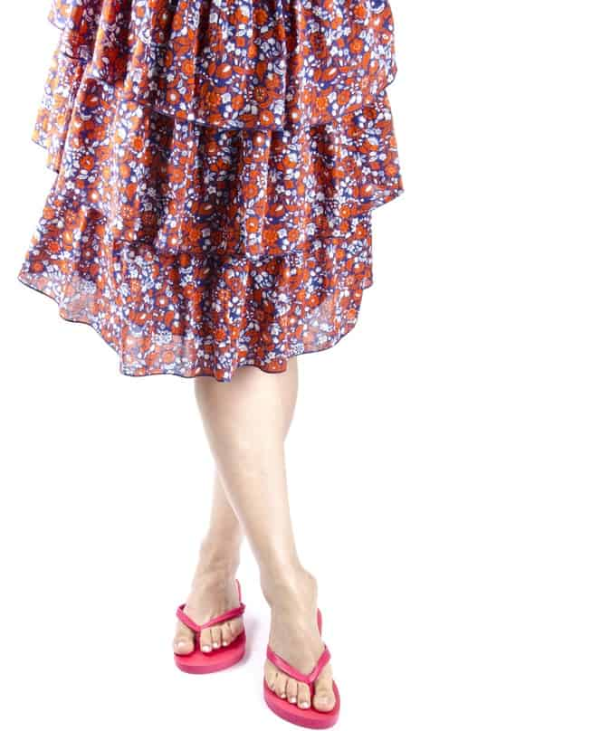 This is a woman wearing a floral layered skirt and a pair of flip-flops.