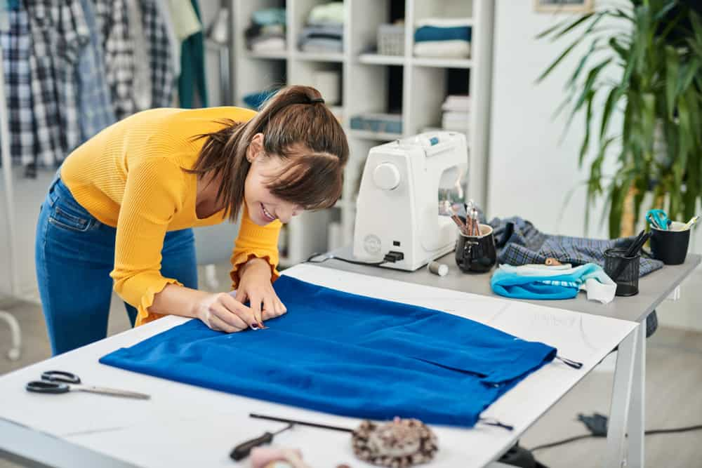 This is a seamstress working on a blue skirt.