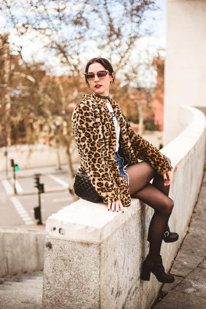 This is a fashionable woman wearing a leopard jacket, a denim skirt and leggings underneath.