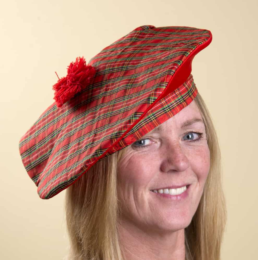 This is a close look at a woman wearing a red patterned Scottish tam o'shanter.