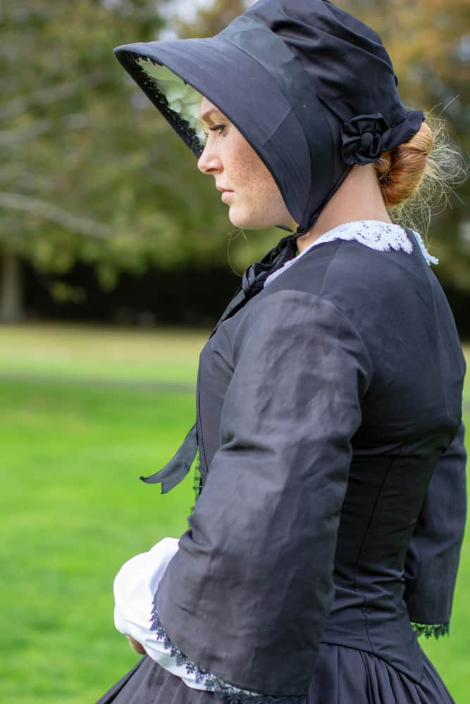This is a woman wearing a vintage mourning dress with matching mourning bonnet.