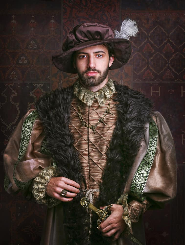 This is a man wearing a vintage 16th Century costume topped with a feathered historical bonnet.