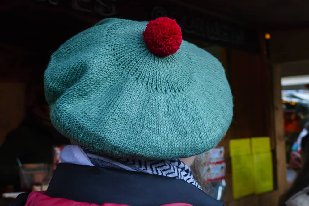 This is a close look at a man wearing a traditional knitted tam cap.