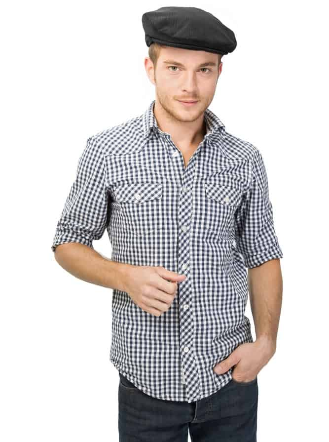 This is a man wearing a patterned button shirt with his ivy cap.