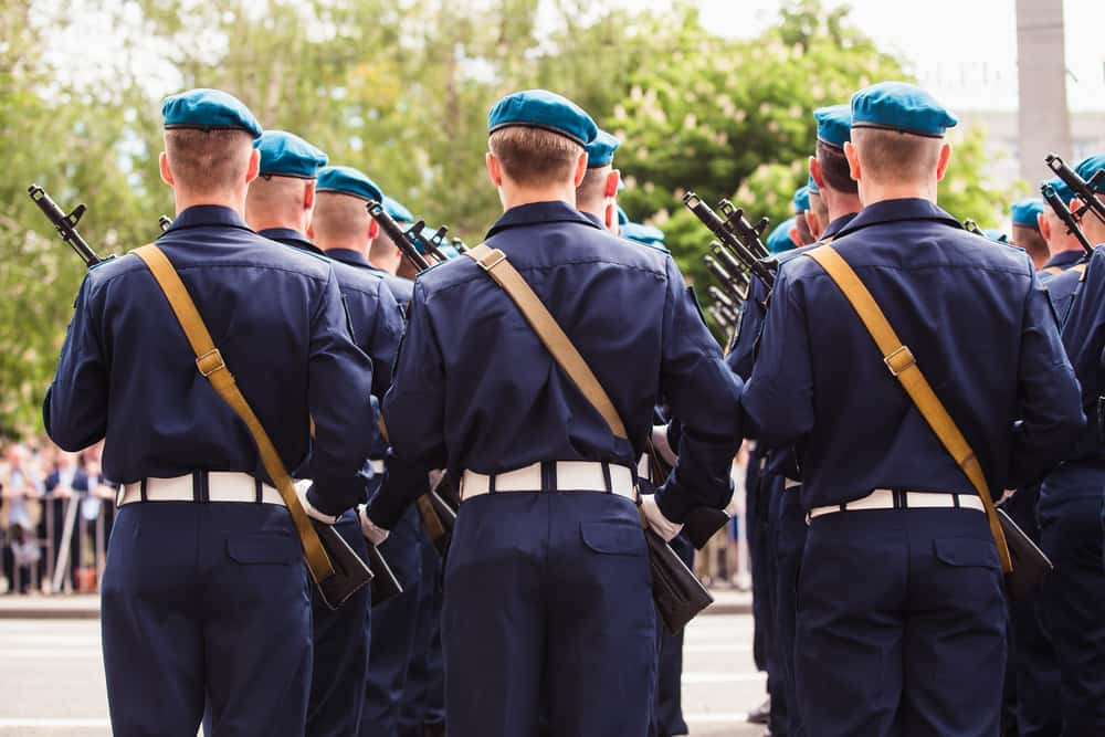 These are military soldiers wearing a dark blue uniform topped with blue bonnets.