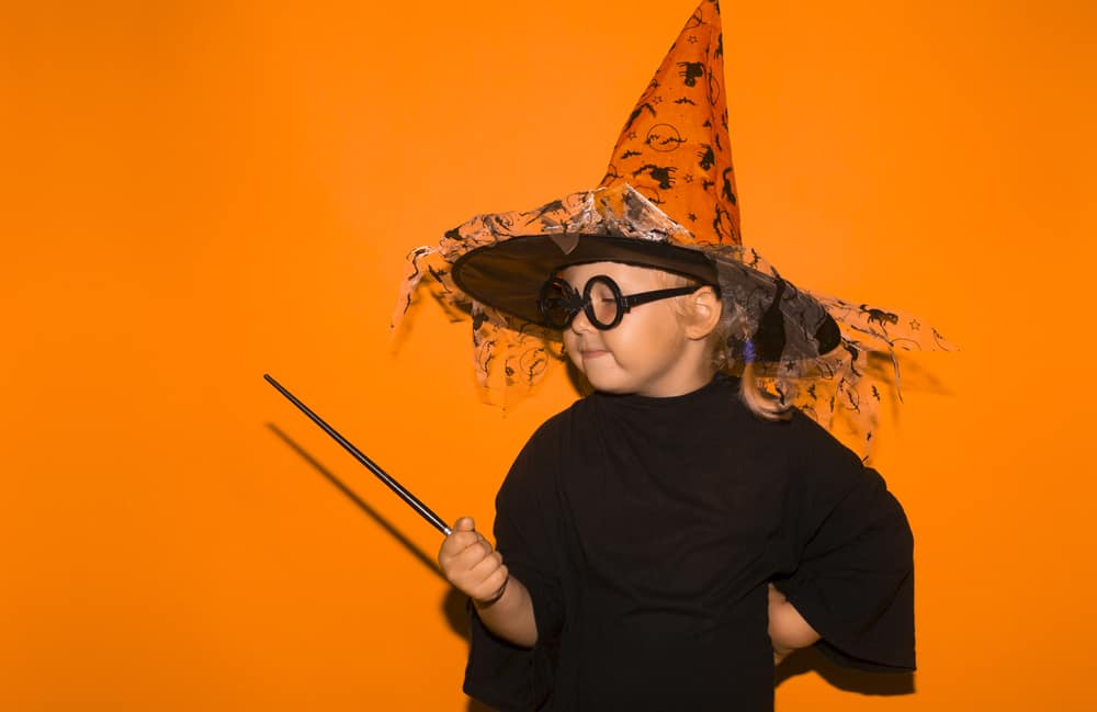 This is a child wearing a Halloween costume as a witch.
