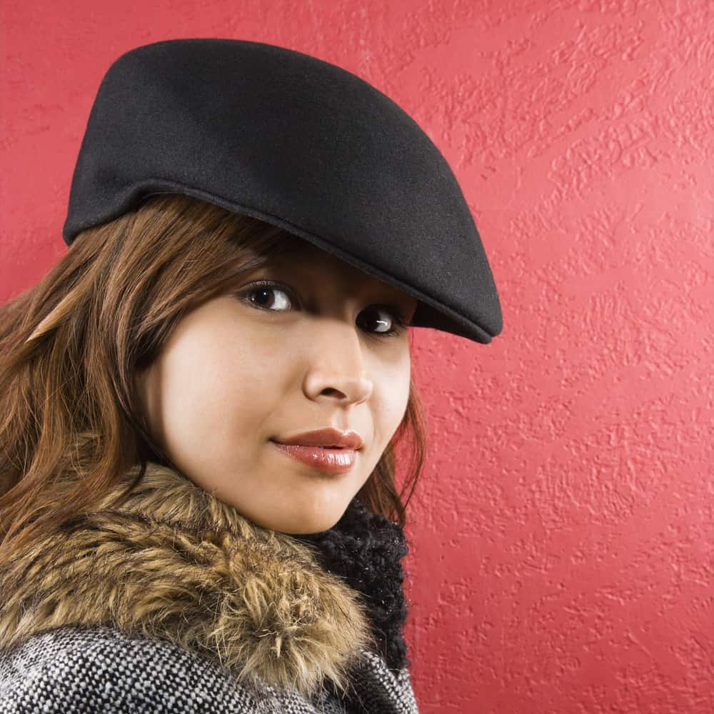 This is a close look at a woman wearing a fur-lined jacket with her black ivy cap.