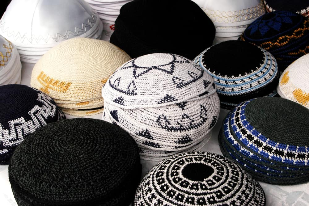 A collection of knitted yarmulkes in various patterns and colors.