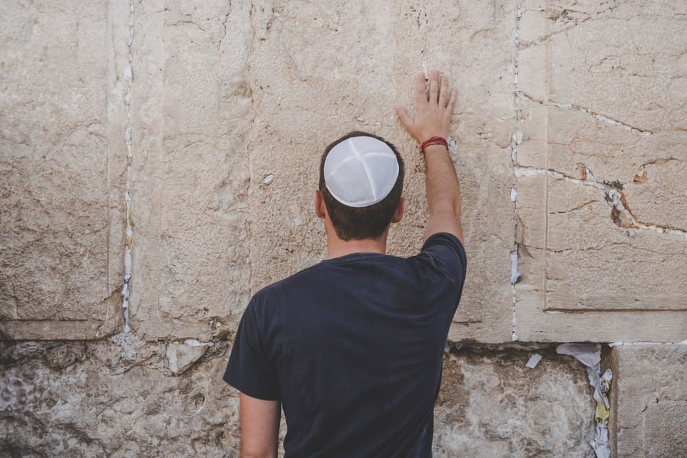 A man wearing linen kippah places his hand and pray on the Wailing Wall.