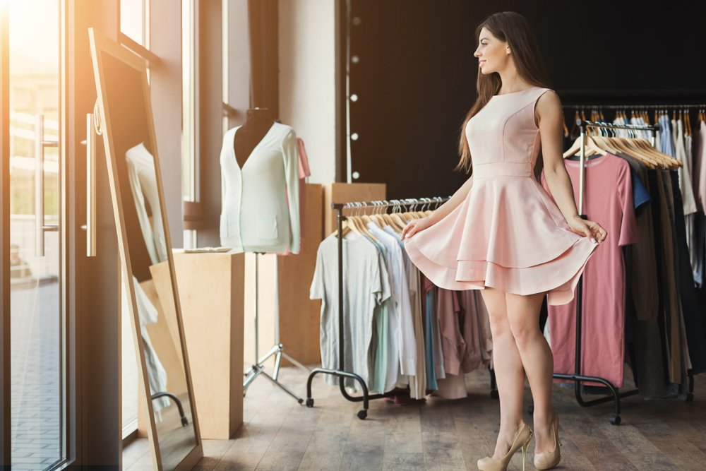 Woman trying on a dress in front of a window surrounded by clothes