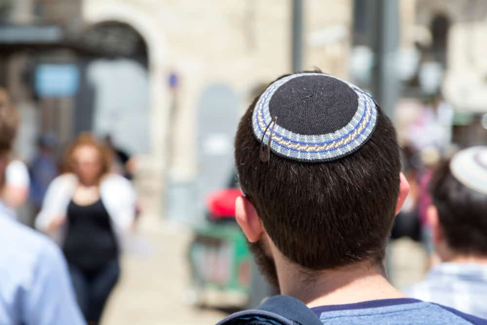 Back profile of a Jewish man wearing Yemenite yarmulke walking down the street.