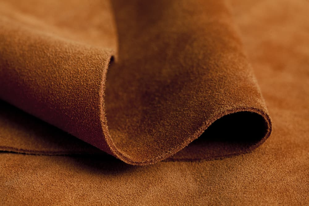 This is a close look at a piece of brown leather suede fabric.