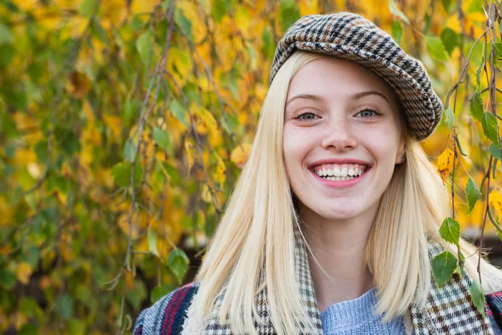 A girl wearing a checkered kepi hat to match her scarf.