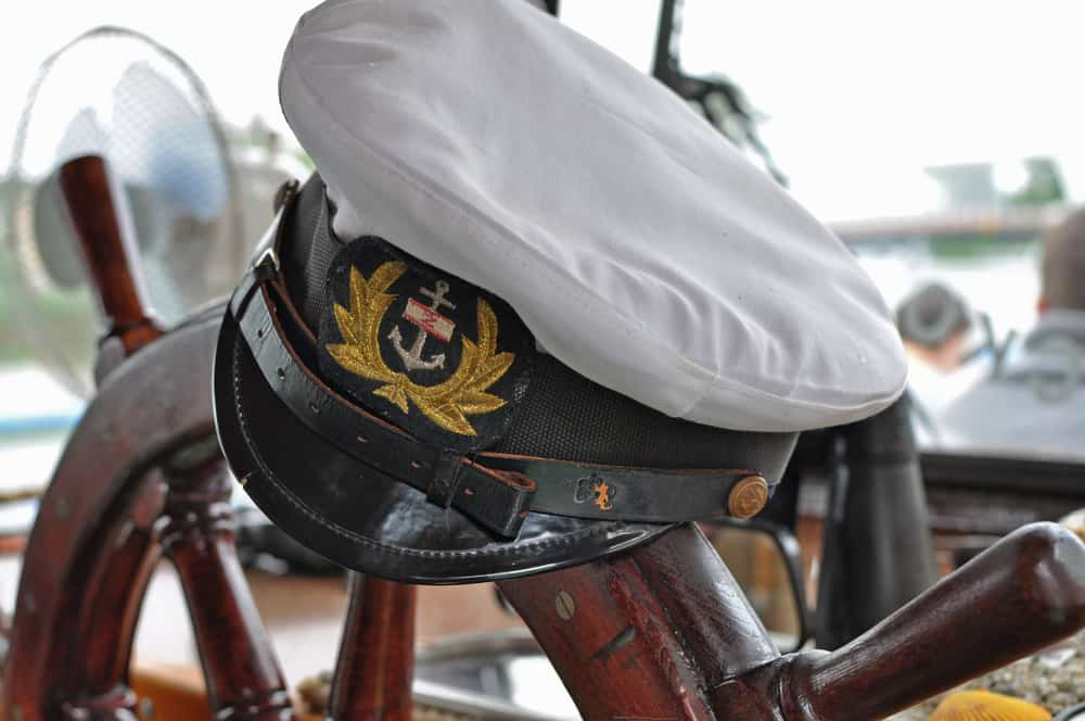 This is a close look at the captain's sailor hat on the boat steering wheel.