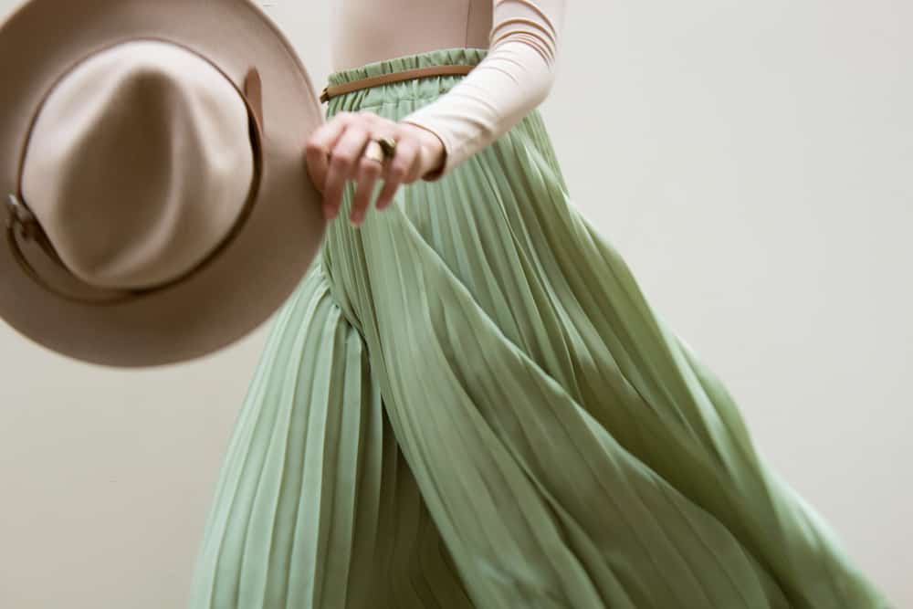 This is a close look at a woman wearing a green skirt, beige blouse and beige hat.
