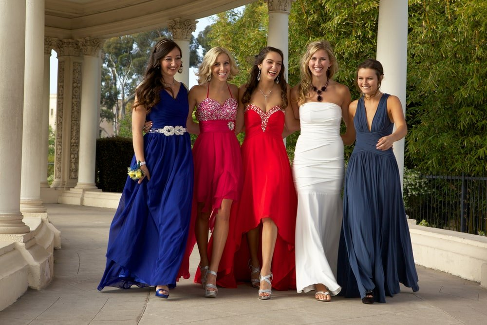 A group of women wearing formal dresses to prom.