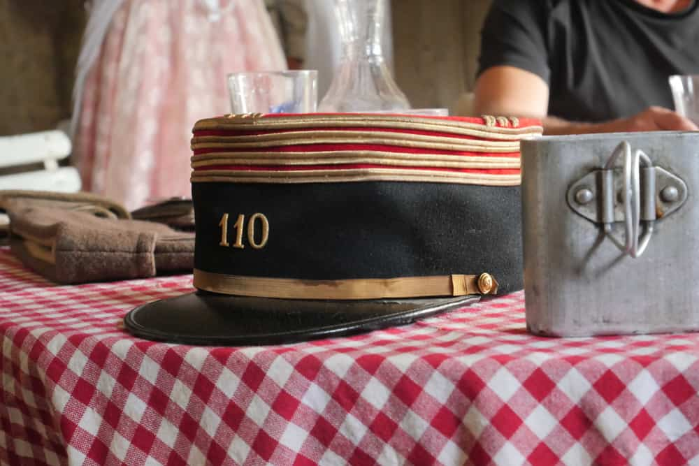 This is an antique French military kepi hat on a table on display.
