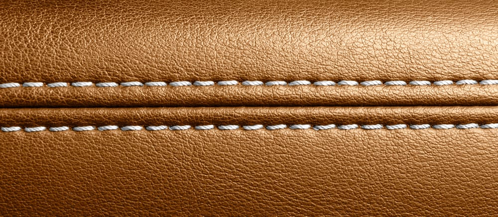 This is a close look at the white stitching of a brown leather upholstery.
