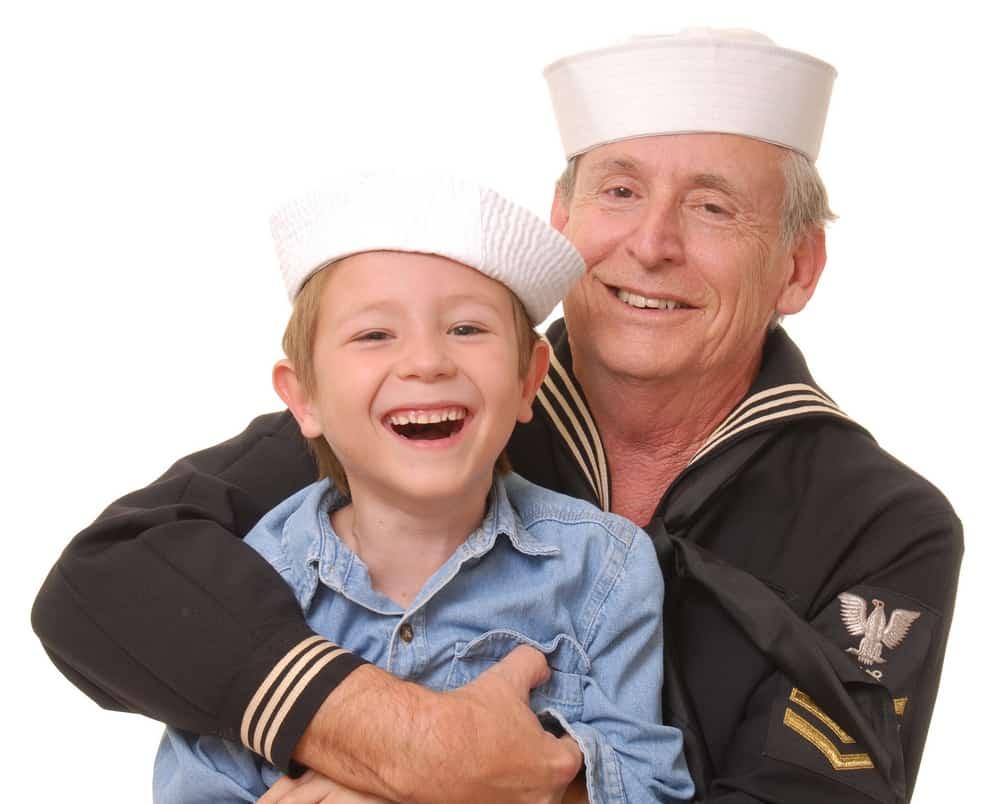 A father and son wearing vintage sailor Navy uniforms.