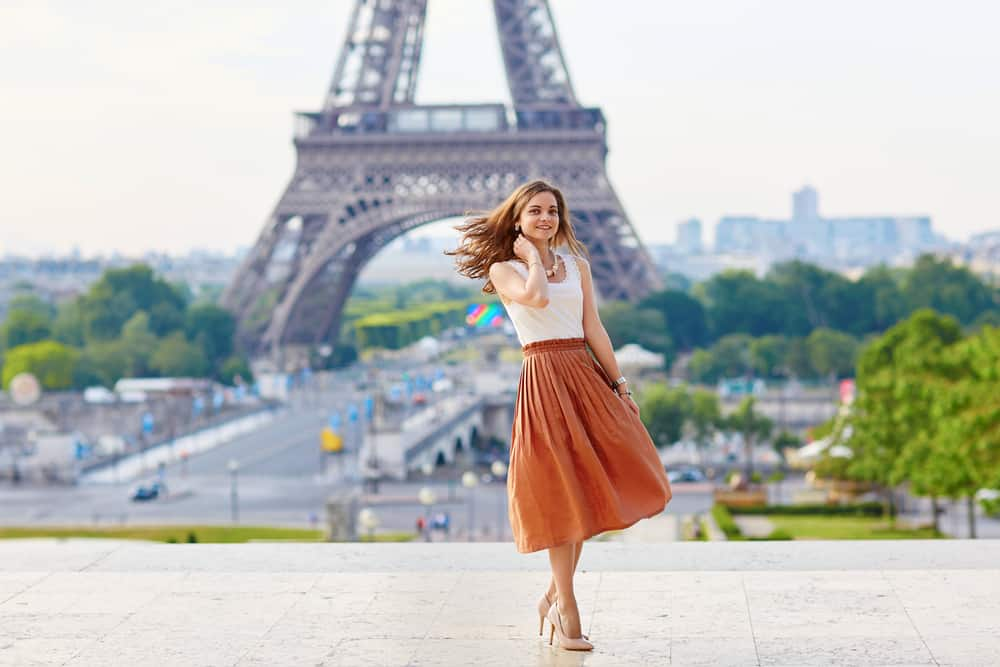 A Parisian woman wearing a long skirt with her white blouse and heels.