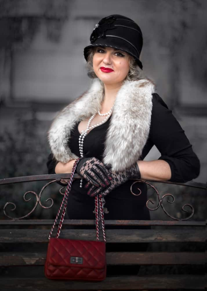 This is a woman wearing a dark vintage outfit with a clochet hat.