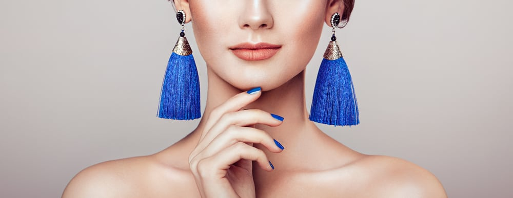 This is a close look at a woman wearing a blue tassels earrings.