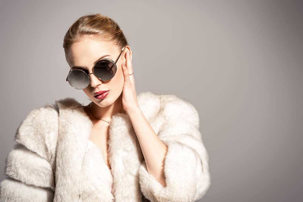 This is a woman wearing a white fur coat a pair of sunglasses.