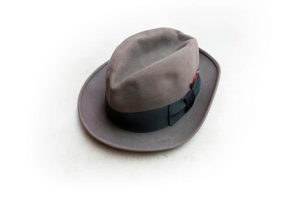 A gray homburg hat with a dark band and feathers.