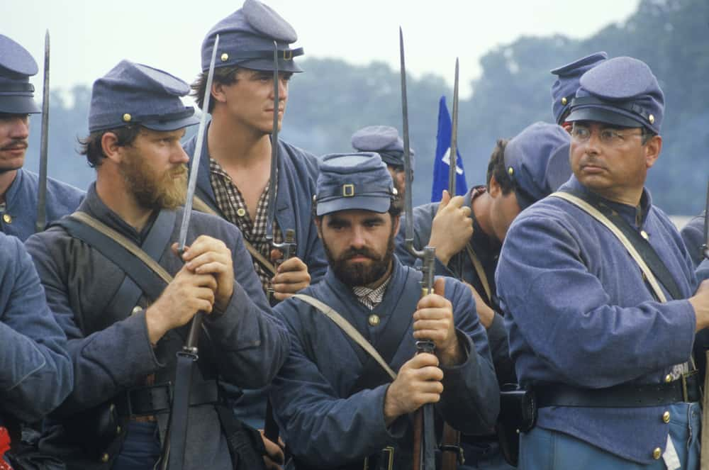 This is a historical reenactment of the civil war with soldiers wearing blue uniforms and kepi hats.