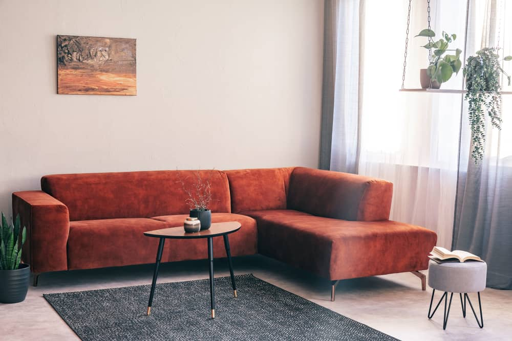 This is a living room with a reddish brown suede sectional sofa.