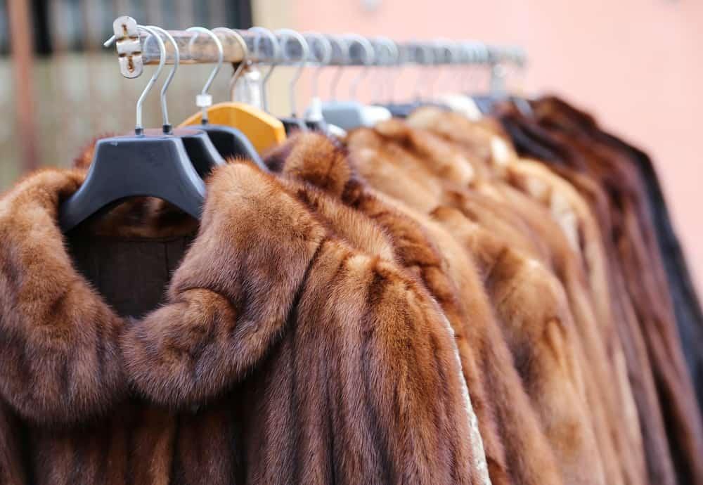 A row of luxury fur coats on display on a rack.