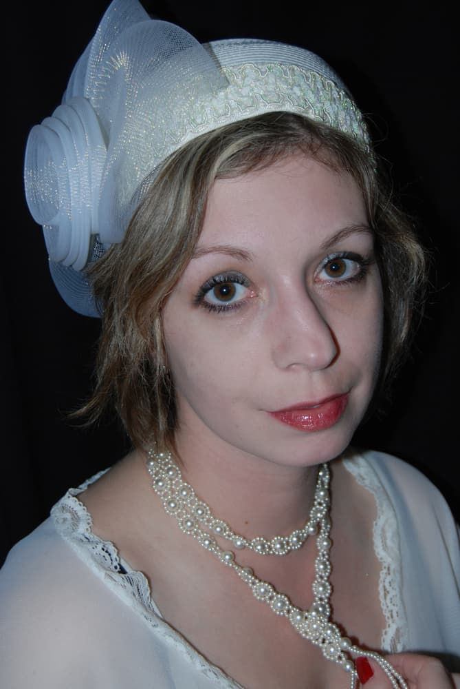 This is a close look at a woman wearing a vintage 1920s attire with a pillbox hat.