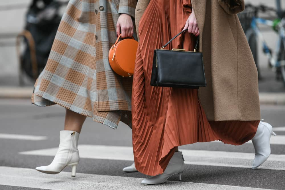 A close look at stylish women crossing the street wearing skirts and heels.