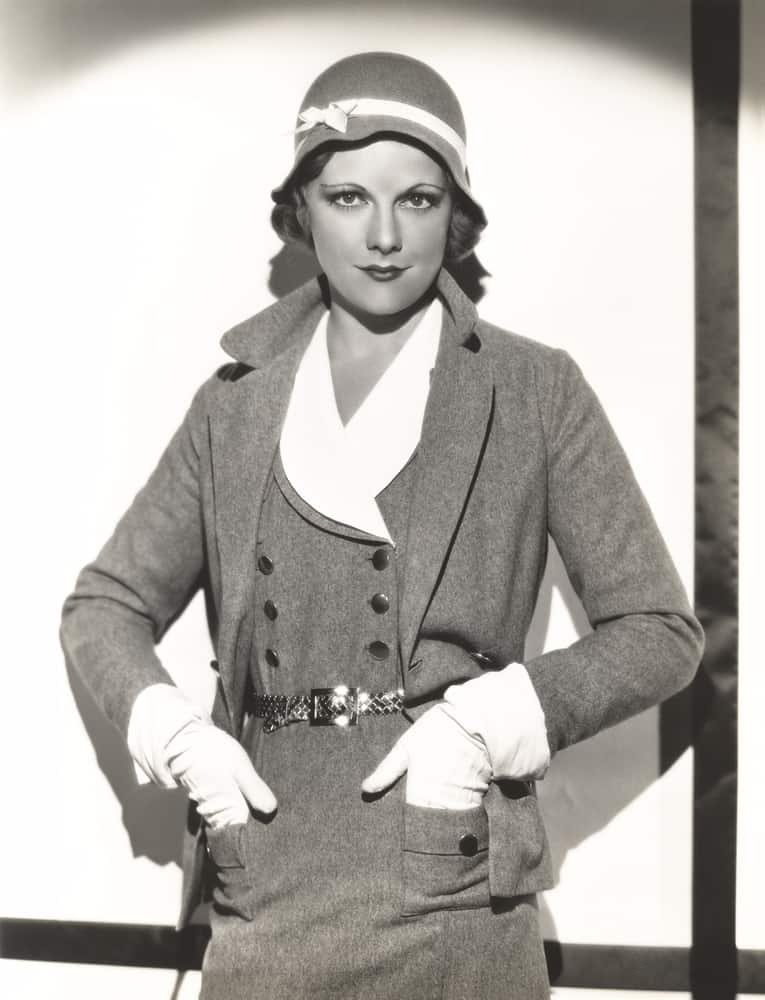 This is a black and white image of a woman wearing a dress suit and a clochet hat.