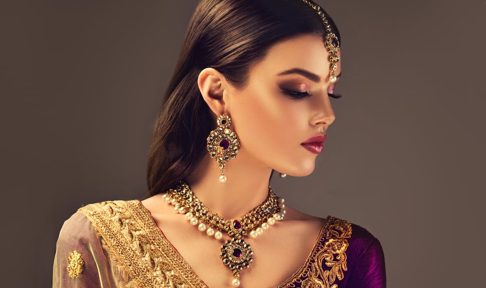 This is an Indian woman wearing a traditional sari and a set of traditional jewelry.