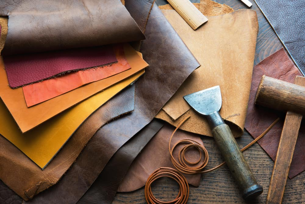 This is a close look at the leather fabrics and leather making tools on the work table.
