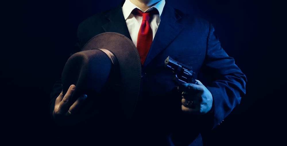 This is a close look at a man in a suit carrying a gun and a homburg hat.