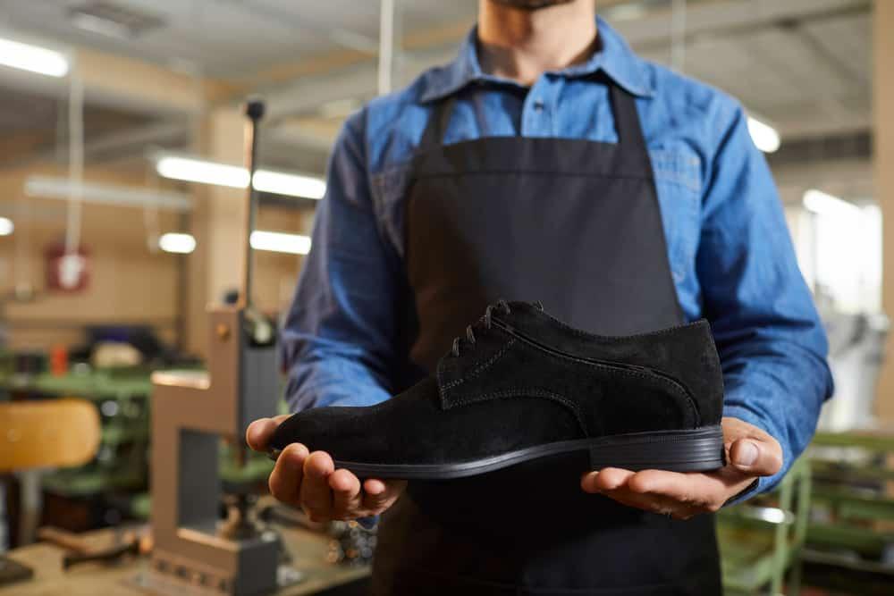 A shoemaker holding a finished black suede shoe.