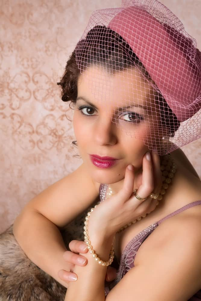 This is a woman wearing a vintage pink pillbox hat with netting.