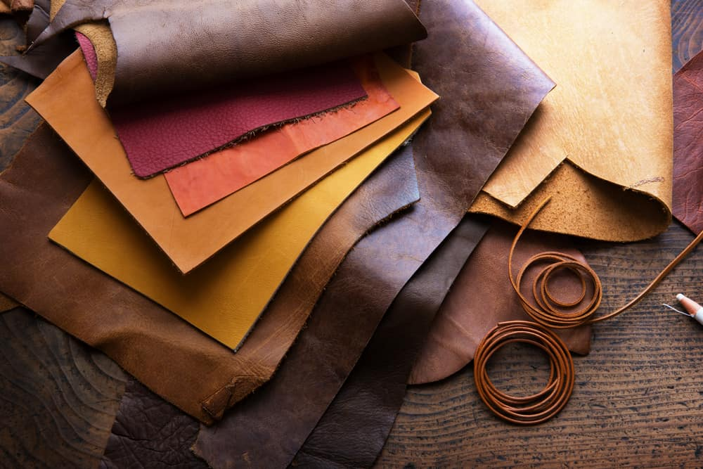 These are various leather pieces on a wooden work table.