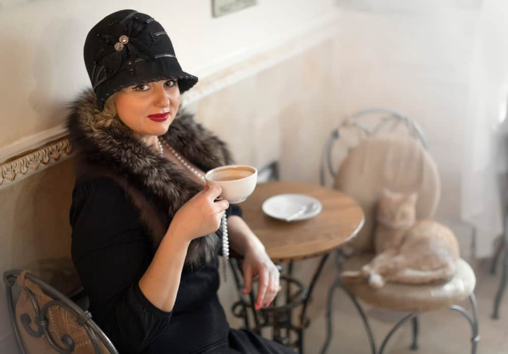 A woman wearing a vintage dark outfit while drinking tea.
