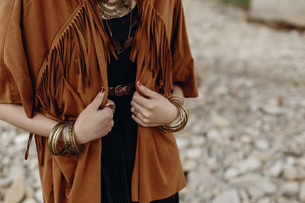 A woman wearing a brown fringe suede jacket.