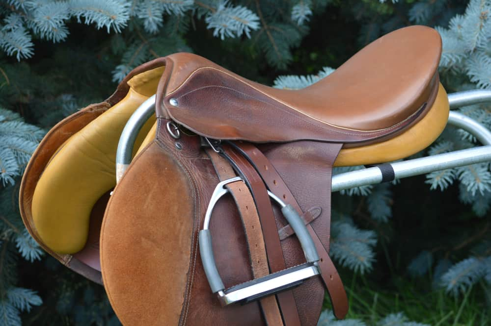 This is a brown leather suede riding saddle on display.