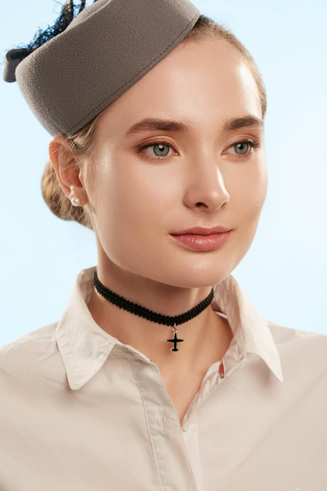 This is a close look at a woman wearing a brown pillbox hat with her button shirt.